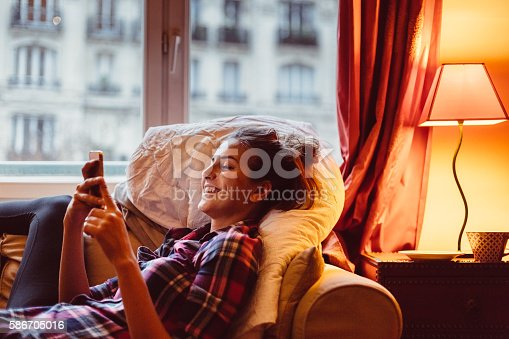 Happy woman at home text messaging