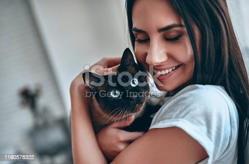 Attractive young woman at home with blue-eyed cat.