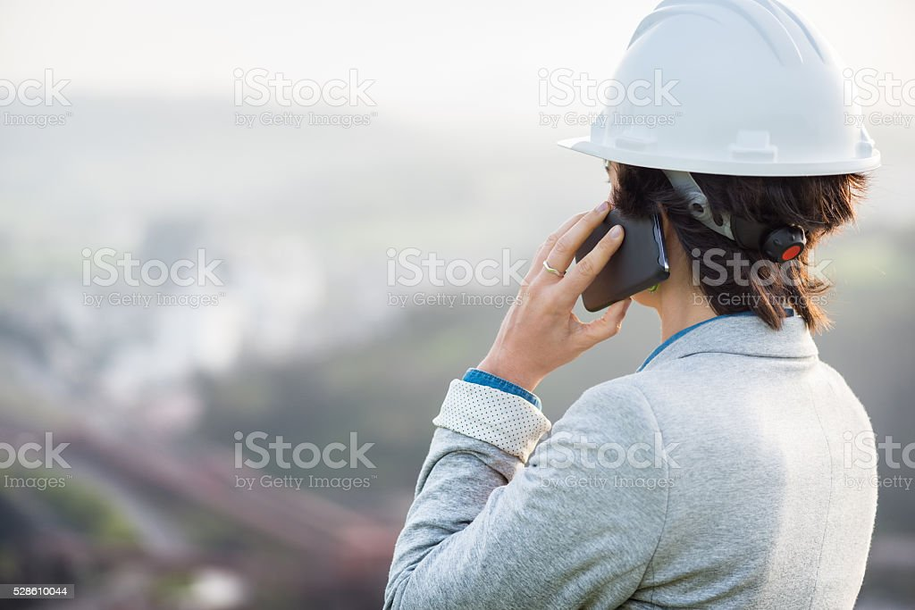 woman at industry with safety helmet showing back on phone stock photo