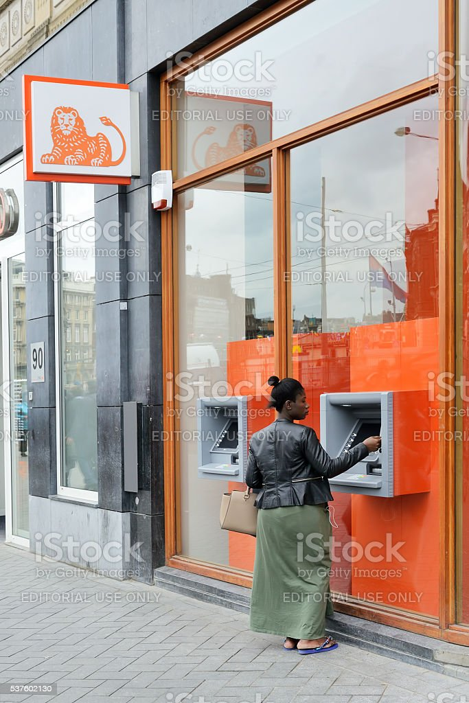 Woman at ING Bank ATM stock photo