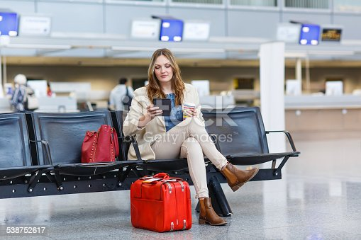 istock woman at international airport, reading ebook and drinking coffe 538752617