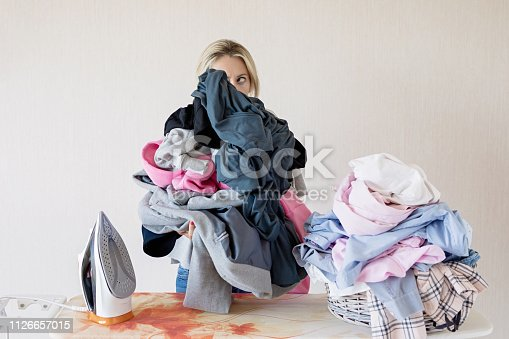 istock Woman at ironing desk behind pile of clothes 1126657015