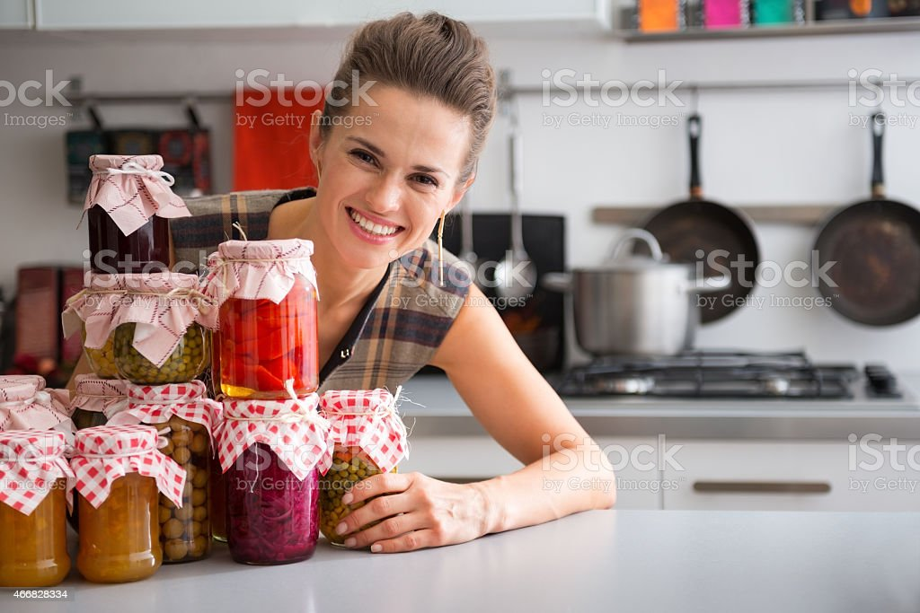 Woman at kitchen table with stack of jam and pickle jars stock photo