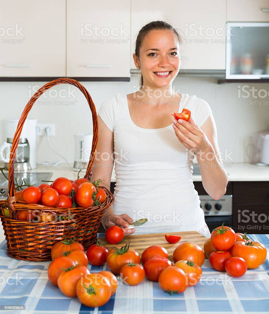 Woman at kitchen with tomatoes on the table stock photo