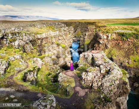Young woman embracing nature high above the canyon of Koluglijufur, Iceland