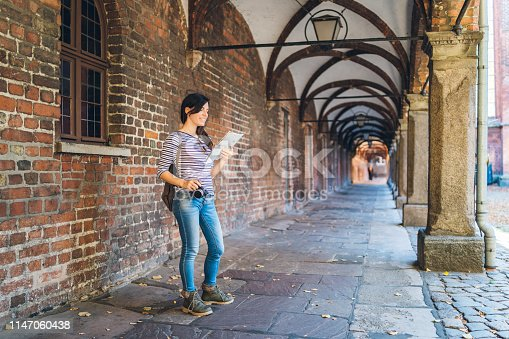 Young tourist woman is exploring Lubeck old town with camera and a map