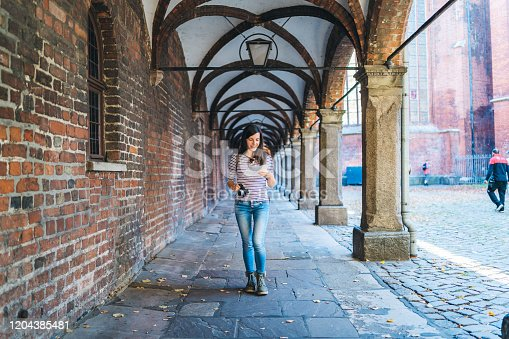 Young tourist woman is exploring Lubeck old town with camera and a map.