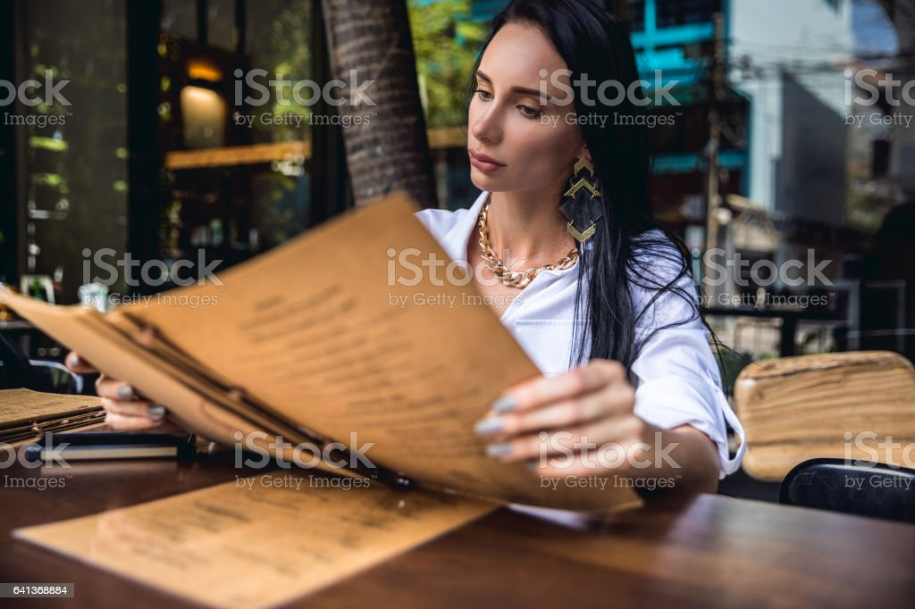 Woman at lunch break sitting in outdoor restaurant bar stock photo