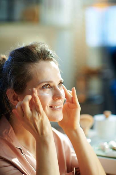 woman at modern home in sunny winter day applying eye cream stock photo