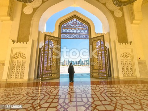 Woman with abaya dress looks at views of skyscrapers of Doha West Bay skyline outdoors State Grand Mosque in Doha, Qatar, Middle East, Arabian Peninsula.