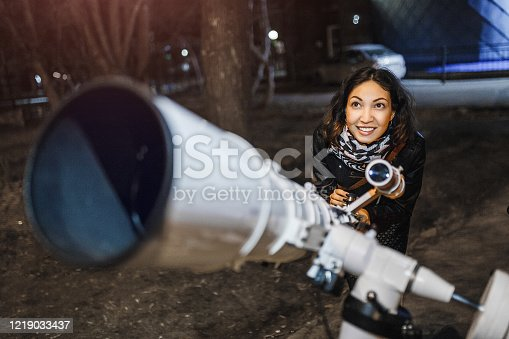 Woman at night looks at the starry sky in a large professional telescope and smiles