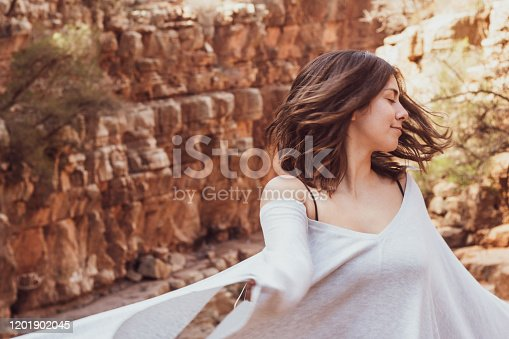 Woman in flowing robe and swimsuit at an oasis in the mountain of Morocco