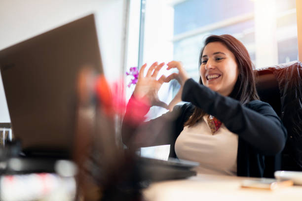Woman at office video chatting, and making heart shape Woman at office video chatting, and making heart shape long distance relationship stock pictures, royalty-free photos & images