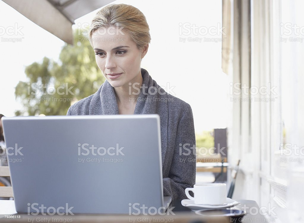 Woman at outdoor patio table on laptop royalty-free stock photo