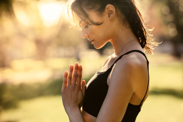 Woman at park practising meditation Fitness woman doing yoga with her hands joined and eyes closed. Female standing outdoors and practising meditation. prayer pose yoga stock pictures, royalty-free photos & images