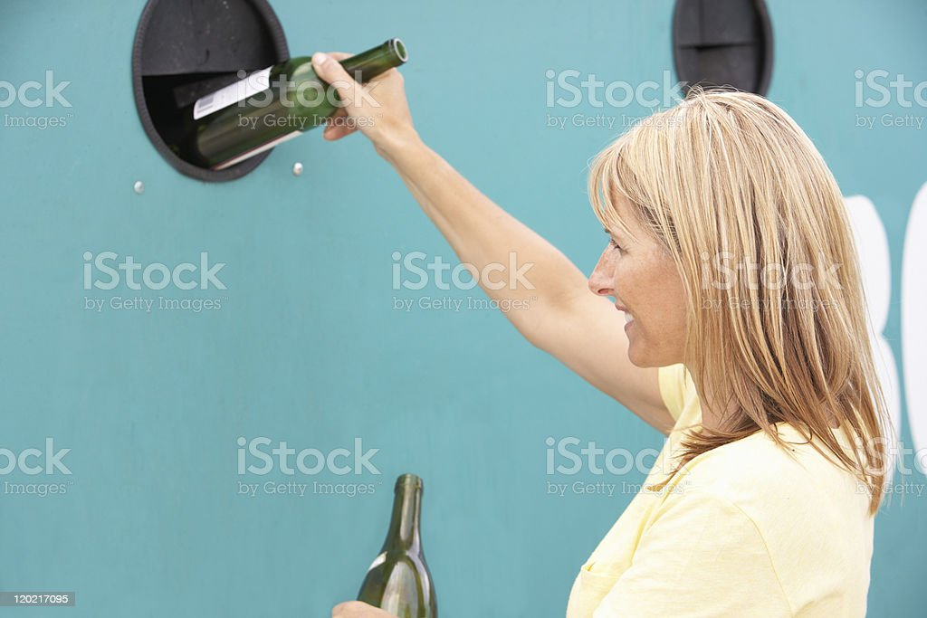 Woman At Recycling Centre Disposing Of Glass Bottles stock photo