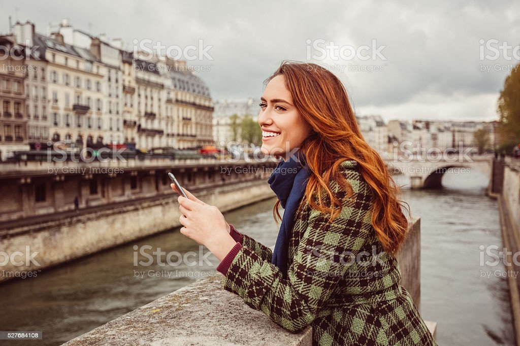 Woman at Seine river texting stock photo