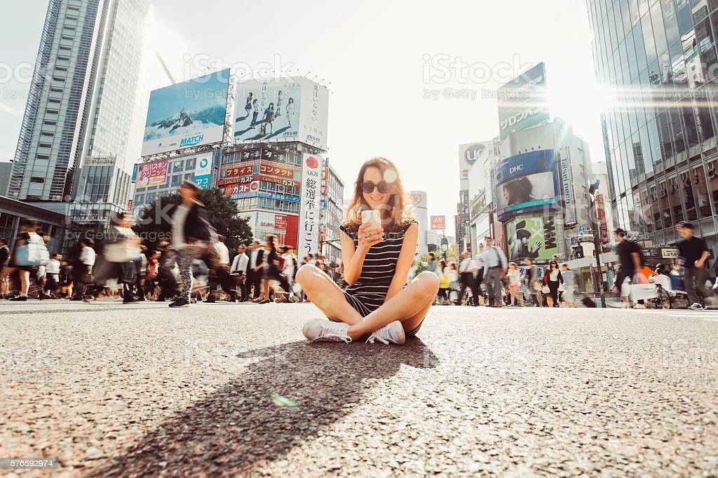 Woman at Shibuya crossing text messaging stock photo
