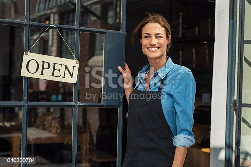 Portrait of a happy waitress standing at restaurant entrance. Portrait of mature business woman in black apron ready to attend new customers in her just opened coffee shop. Happy beautiful woman owner showing open sign in her small business shop.