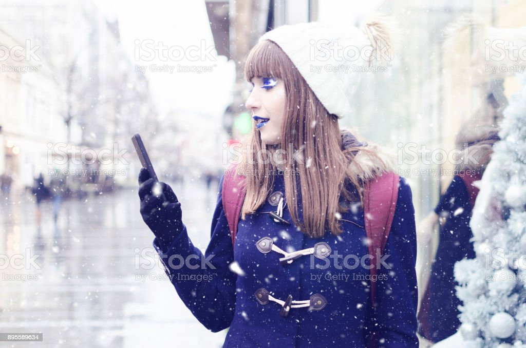 Woman at snow street with mobile phone stock photo
