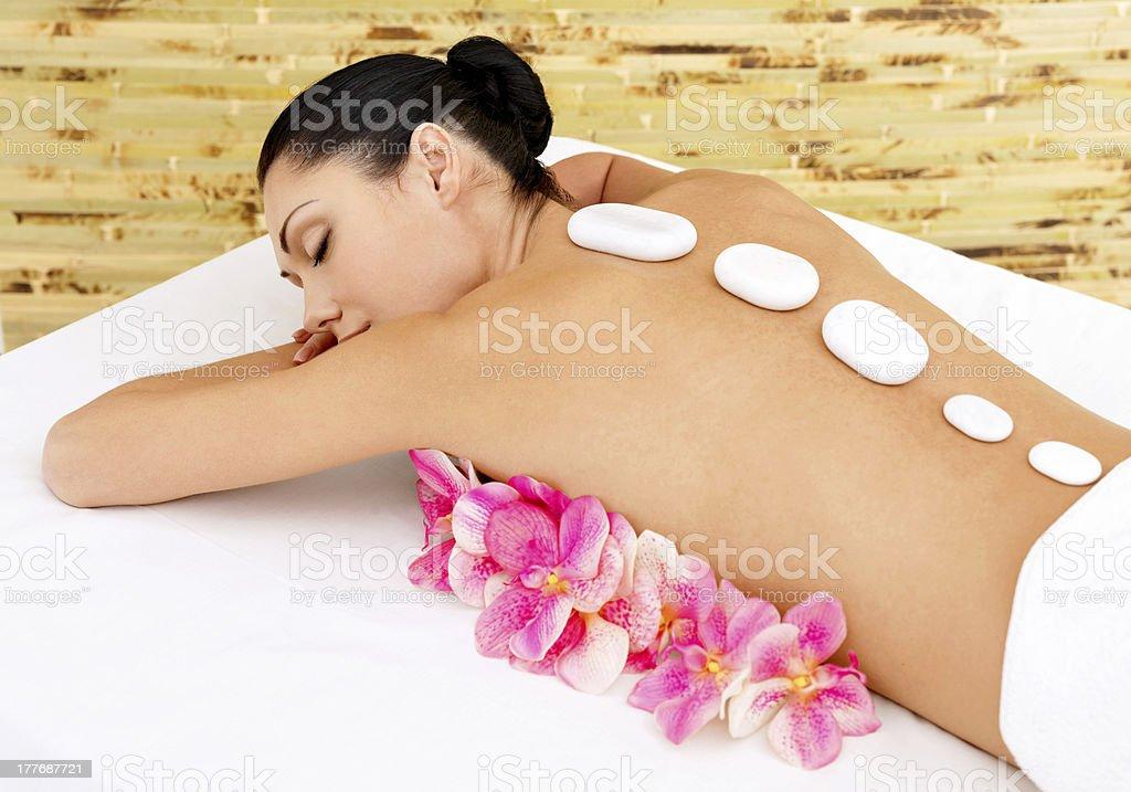 Woman at spa salon. White нot stones on female back. royalty-free stock photo