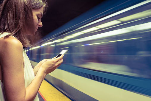 Woman at subway station using smartphone to see the map