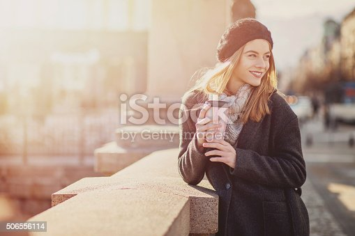 531098549 istock photo Woman at sunlight holding coffee and smiling 506556114