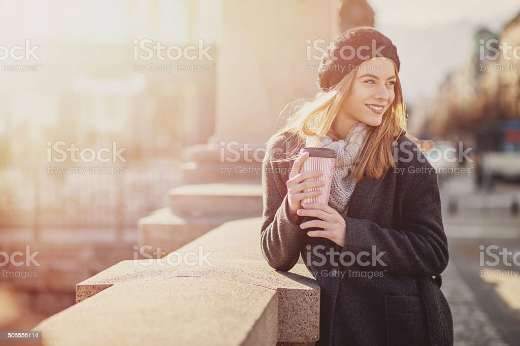 Woman at sunlight holding coffee and smiling stock photo