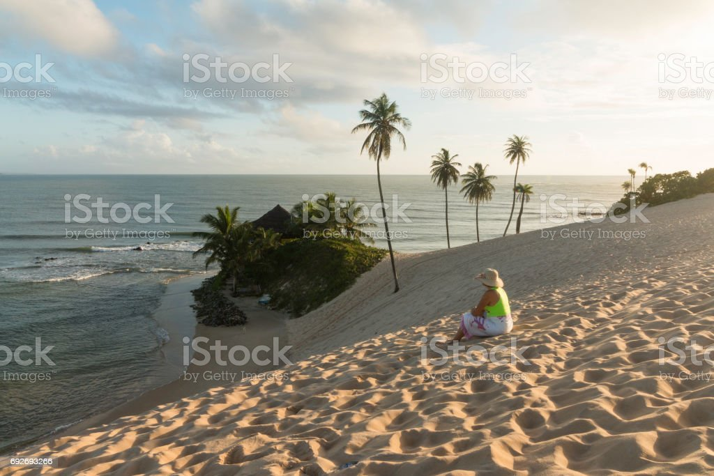 Woman at sunrise in Genipabu dunes and beach stock photo