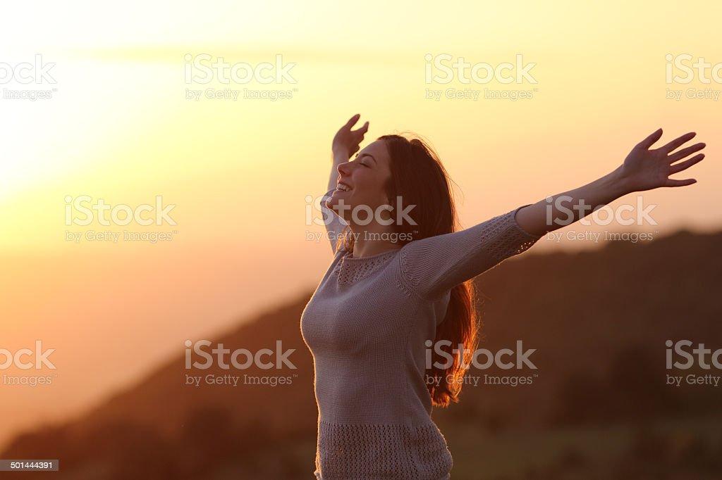 Mulher no pôr do sol, respirar ar fresco aumentar os braços foto de stock royalty-free