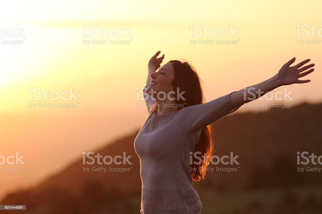 Woman at sunset breathing fresh air raising arms stock photo