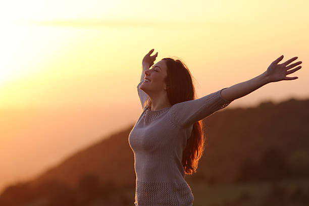 woman at sunset breathing fresh air raising arms - arms outstretched stock photos and pictures