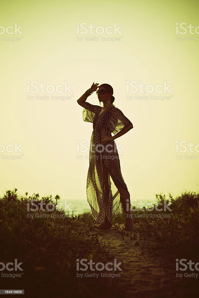 Woman at sunset Young woman looking in a distance on the coast at sunset. Adult Stock Photo