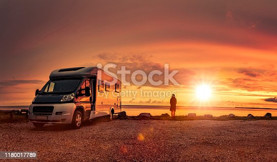 Woman at sunset  with mobile home on the beach