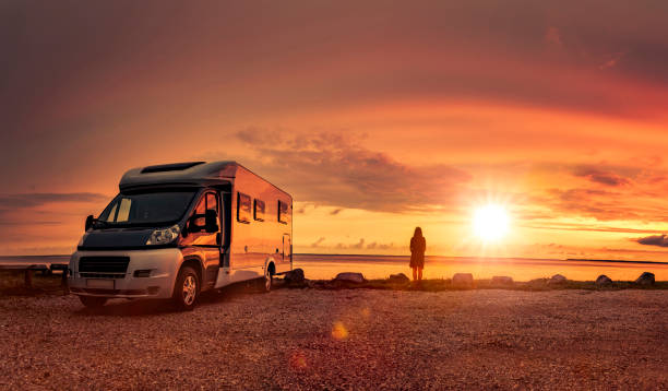 woman at sunset  with mobile home on the beach - camping imagens e fotografias de stock