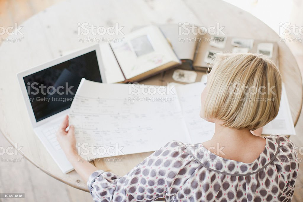 Woman at table looking at genealogical tree royalty-free stock photo