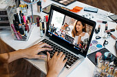 Woman at table with laptop between makeup kits watching beauty video