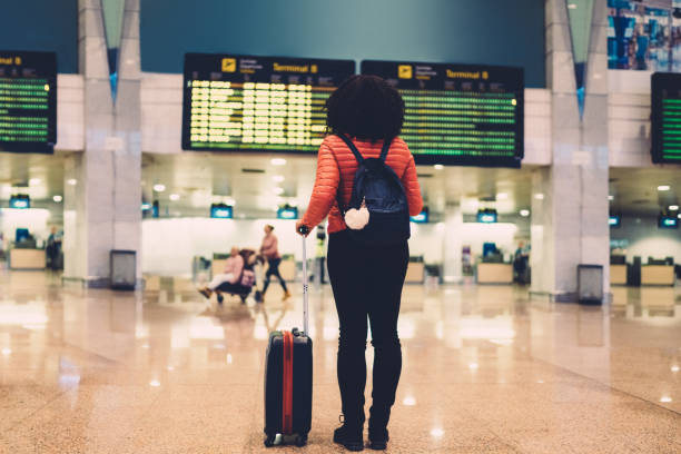 Woman at the airport checking the arrival departure board stock photo
