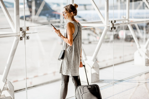Young woman standing with phone near the airport window waiting for the flight
