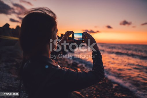 Woman on beach holiday taking photos with smartphone on sunset