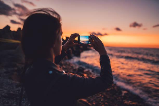 frau am strand den sonnenuntergang fotografieren - fotografische themen stock-fotos und bilder