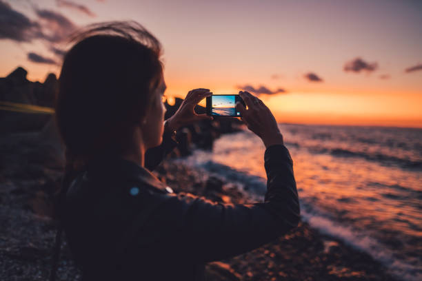 Woman at the beach photographing the sunset stock photo