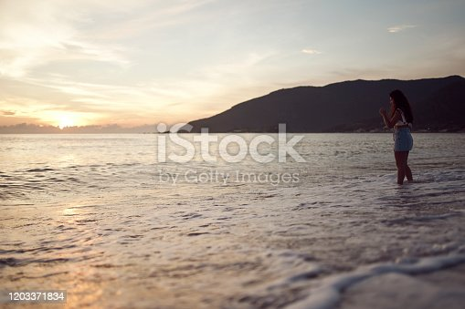 928866530 istock photo Woman at the beach 1203371834