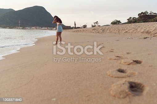 928866530 istock photo Woman at the beach 1203371840