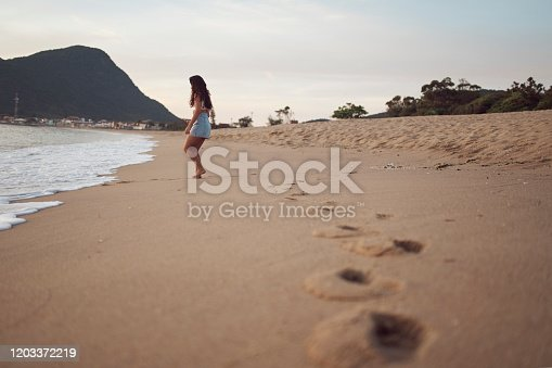 928866530 istock photo Woman at the beach 1203372219