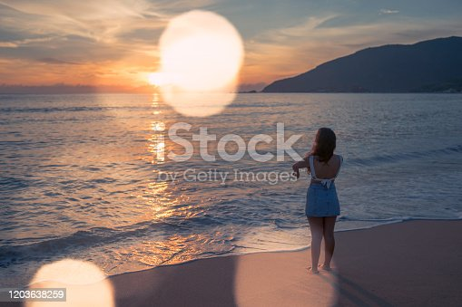 928866530 istock photo Woman at the beach 1203638259