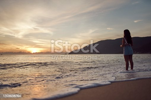 928866530 istock photo Woman at the beach 1203638264