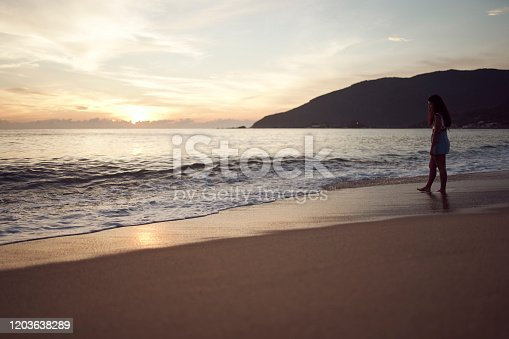 928866530 istock photo Woman at the beach 1203638289