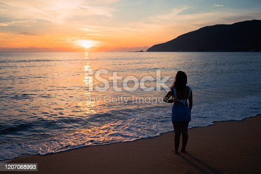 928866530 istock photo Woman at the beach 1207068993