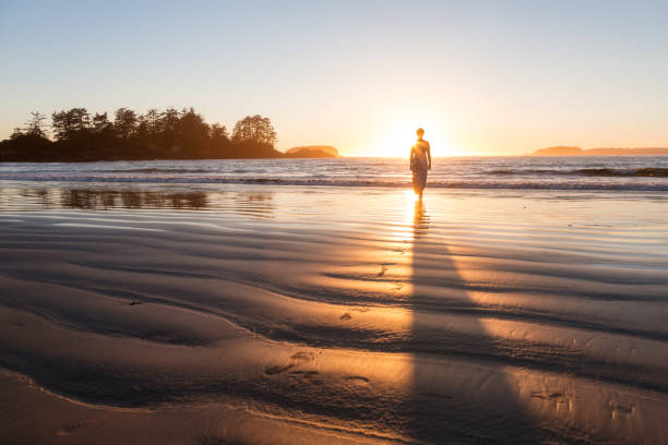 Woman at the Beach Woman in a casual dress is walking bare feet on a sandy beach during a colorful and vibrant sunset. Taken in Tofino, Vancouver Island, British Columbia, Canada. vancouver island stock pictures, royalty-free photos & images